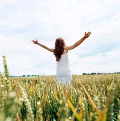 prayer-woman-in-field-with-arms-stretch